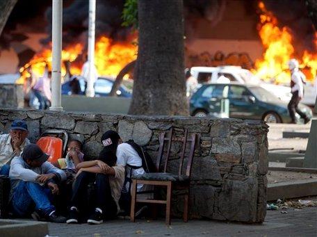 Gente se protege de acciones violentas mientras al fondo se observan vehículos que fueron incendiados durante disturbios ocurridos en una manifestación de opositores en Caracas, Venezuela, el miércoles 12 de febrero de 2014. Dos hombres fallecieron y cuatro resultaron heridos a consecuencia de disparos de arma de fuego durante unos violentos incidentes. (AP Photo/Alejandro Cegarra)