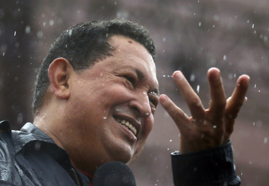 Venezuela's President and presidential candidate Hugo Chavez speaks in the rain during his closing campaign rally in Caracas